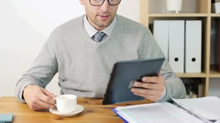 Young happy businessman drinking coffee and using tablet during break