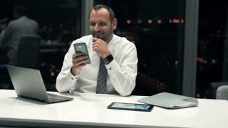 Young, happy businessman sitting with smartphone by desk during night in the office