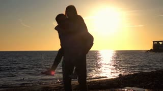 Young, happy couple having fun on beach, slow motion shot at 240fps