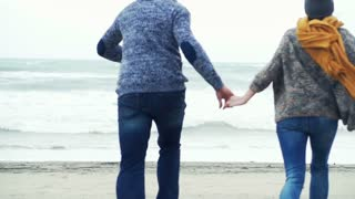 Young happy couple running to the beach and turning round on a stormy day, 240fps