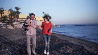 Young happy couple s walking with small baby on the beach