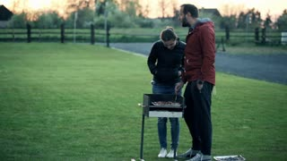 young happy couple talking and grilling in the country