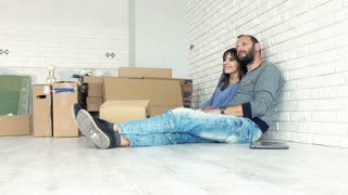 Young, happy couple talking and kissing on floor at their new home, 4K
