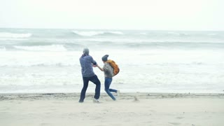 Young happy couple turning round the beach on a stormy day, 240fps