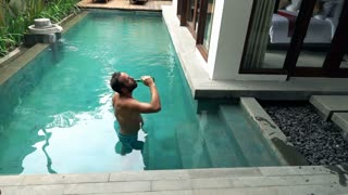 Young, happy man drinking beer in the swimming pool, super slow motion 240fps