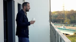 Young, happy man drinking red wine on terrace at home
