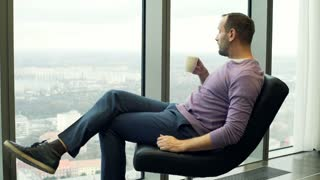 Young, happy man drinking tea on armchair close to the window at home