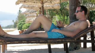 young, happy man listening music while lying on sunbed on beach