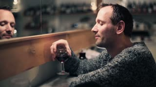 Young happy man raising toast with glass of wine to camera