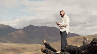 Young happy man standing with smarthone with splendid mountains view behinds