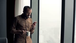 Young, happy man standing with smartphone by the window