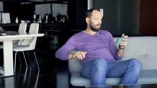 Young happy man watching movie on smartphone sitting on sofa at home
