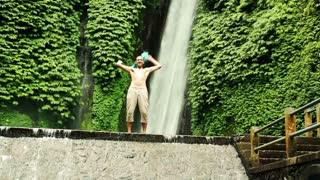 Young happy man waving his shirt by beautiful waterfall In Bali