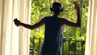 Young  happy woman dancing on terrace with garden view, super slow motion