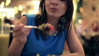Young happy woman eating salad at the restaurant