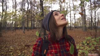 Young happy woman enjoying falling leaves in autumn park super slow motion, shot at 240fps