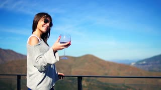 Young, happy woman holding and shaking glass of wine on terrace in the country, super slow motion