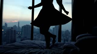 Young happy woman in dress jumping on hotel bed, super slow motion, 240fps