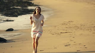 Young, happy woman running on beach, super slow motion, shot at 240fps