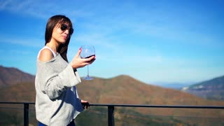 Young, happy woman shaking and drinking glass of wine on terrace in the country