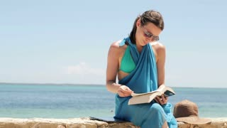 young, happy woman sitting on the seashore and reading book