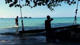 Young, happy woman sitting on the swing looking at man walking through the sea, slow motion shot at 120fps