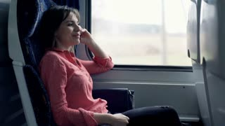 Young, happy woman talking on cellphone sitting on the train