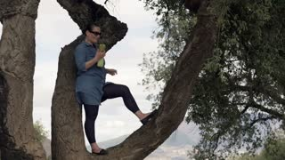 Young happy woman talking on celphone while standing on the tree in the country