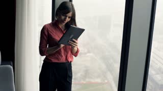 Young, happy woman using tablet computer standing by window