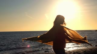 Young, happy woman with scarf turning round on beach during sunset, super slow motion