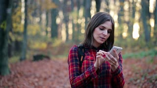 Young hiking woman with smartphone looking for direction in the autumn forest