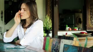 Young impatient woman waiting for someone by table at home