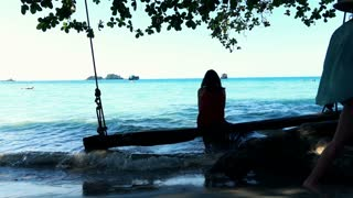 Young lonely woman sitting on beach swing