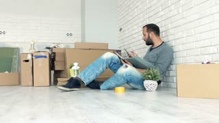 Young man counting bills on smartphone sitting on floor at his new home, 4K