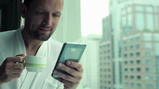 young man drinking coffee and using smartphone by the window with the cityscape view