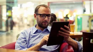 Young man drinking coffee and using tablet in the shopping mall cafe