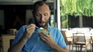 Young man eating delicious ice cream, focus on hands 4K