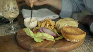 Young man eating french fries and hamburger in cafe, focus on hands, 4K