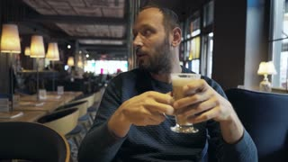 Young man gets his order from waiter sitting in cafe 4K