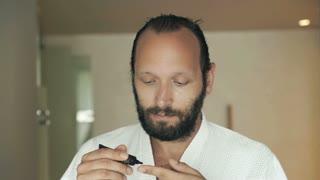 Young man in bathrobe applying anti wrinkle cream on his face in bathroom