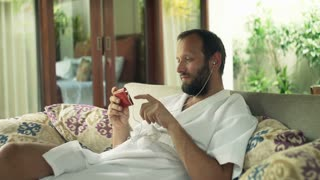Young man in bathrobe watching movie on smartphone sitting on sofa in outdoor villa