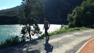 Young man jogging close to the lake, super slow motion