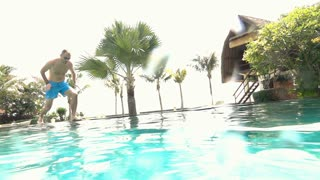 Young man jumping into pool and swimming, super slow motion 240fps