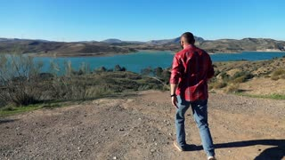 Young man jumping on the beautiful landscape with the lake, super slow motion
