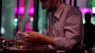 Young man listen to the music on smartphone and drinking beer in cafe at night
