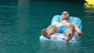 Young man lying on floating mattress in the pool, super slow motion
