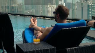 Young man lying on sunbed by pool on roof top in the city, super slow motion