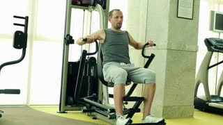 young man performing exercise in the rowing machine