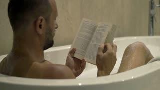 Young man reading book lying in bathtub, 4K