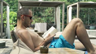 Young man reading book on sunbed, 4K